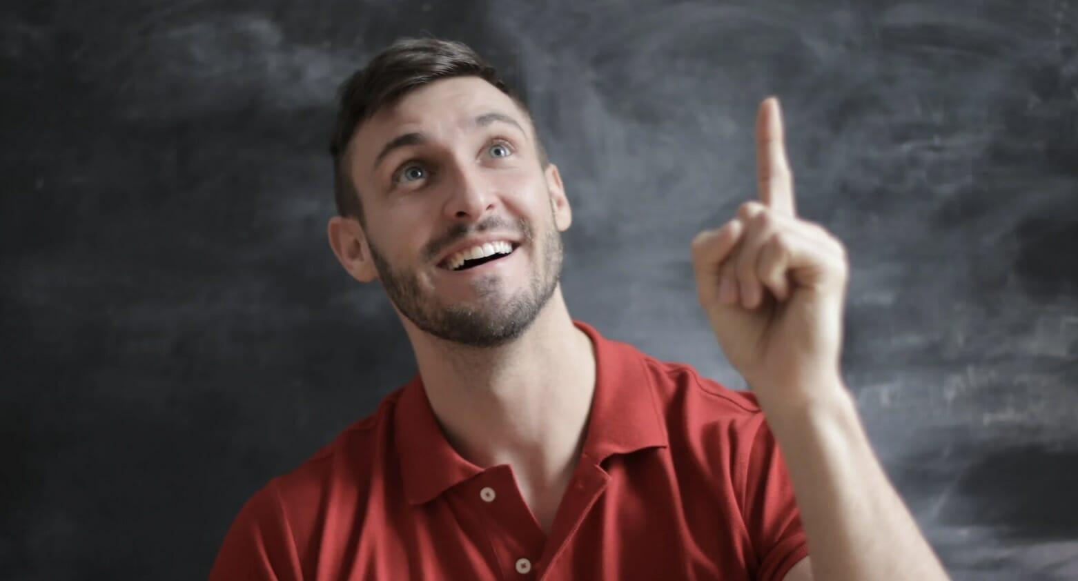 man pointing upward in realization